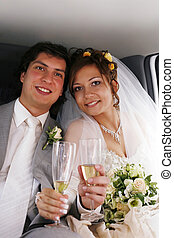 The bride with the groom drinks champagne in the automobile