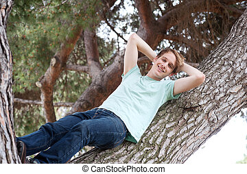 young male relaxing on a tree