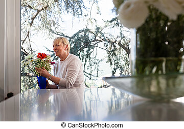 Elderly caucasian woman with flowers at home - Senior...