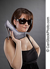 woman with sunglasses holding shoe
