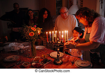 Jewish Holidays Hanukkah - A family is lighting a candle for...
