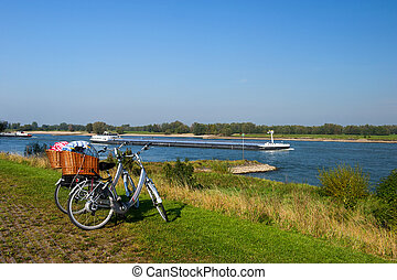 Dutch river landscape with bicycles - Big cargo boat on the...