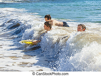boys have fun surfing in the waves - boys have fun riding in...