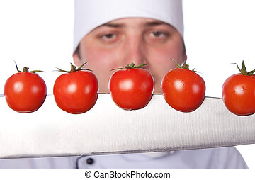 Men cook. cherry tomatoes cut into the knife