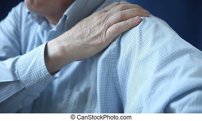 man rubbing sore shoulder