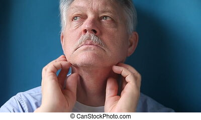 man checking painful lymph nodes - a mature man feels the...
