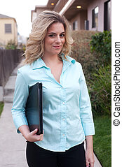 attractive female real estate agent standing outside