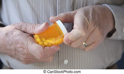 senior shakes out pills - a man gets ready to take his...