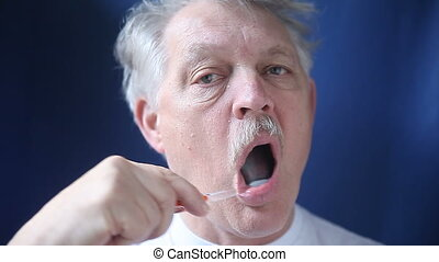 older man brushing his teeth