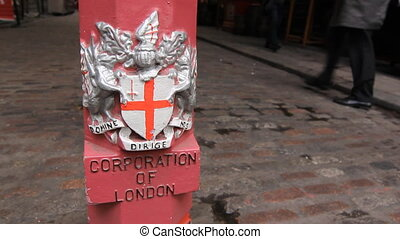Corporation of London bollard. Pedestrians in the...