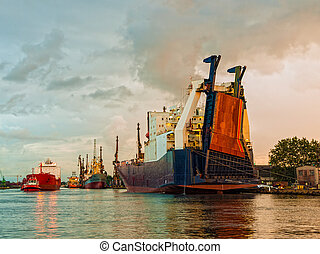 Cargo vessel - Cargo ship in the harbor at sunset Gdansk,...