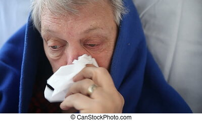 man with flu - a senior man suffering from chills, runny...