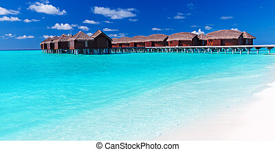 Overwater villas in blue tropical lagoon with white beach -...