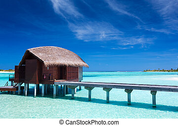 Overwater villas in blue lagoon of an island - Overwater...