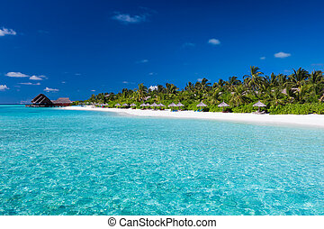 Tropical island with sandy beach and pristine water -...