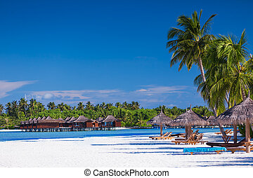 Palm trees over sandy tropical beach with villas over water