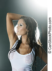 Wet woman in white tank top from profile backlit