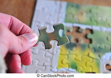 Puzzle Piece - hand putting a puzzle piece in it's spot
