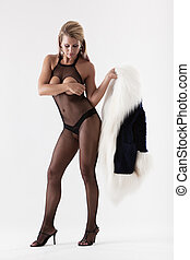 Attractive woman in fishnet lingerie holding fur -...