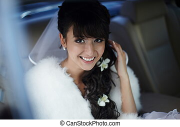 Portrait of beautiful smiling bride with long curly hairsyle bright makeup sitting in car with flowers in hair
