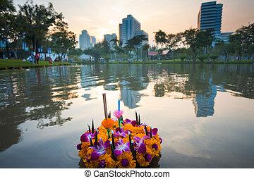 Sunset Loi Krathong Flowers City - A single krathong floats...