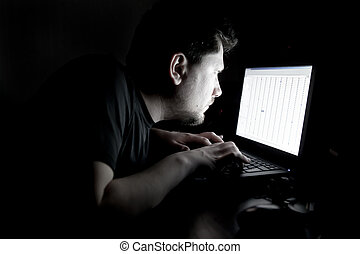 Man working on laptop in the dark - Serious man working on...