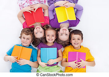 Happy kids laying on the floor holding books - the colorful...