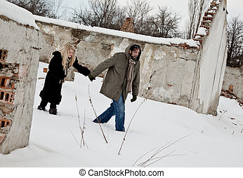 Homeless couple walking in the snow holding hands, struggle...