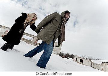 Homeless couple struggle in winter, holding hands and...
