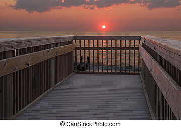 Sun rising over a railing at the beach