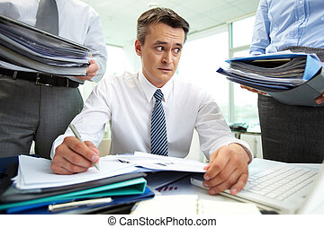 Unexpected work - Shocked accountant looking at huge piles...
