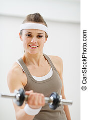 Young woman lifting dumb-bell in the gym
