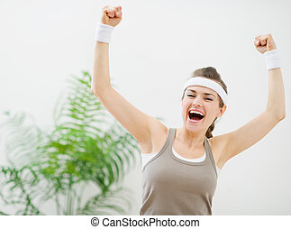 Happy sporty girl rejoicing success