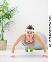 Happy fitness girl making push up exercise