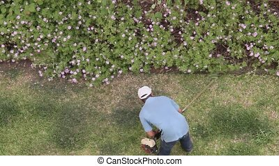 Mowing grass in hard to reach place - Man mowing grass with...