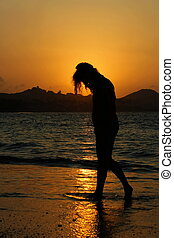 Silhouette woman on beach on sunset