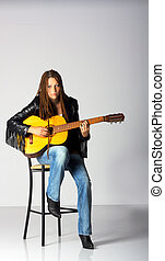 girl in black jacket and blue jeans with guitar