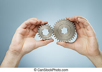 Matching Cogs - Man holding two different sizes metallic cog...