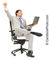 young businessman sitting in chair with laptop - picture of...