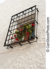 Traditional Andalusian window with red geraniums on the sill