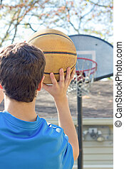 Boy Aiming Basketball - view from back as boy holding...