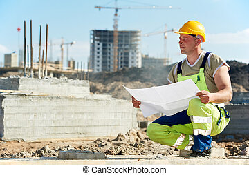 Engineer builders at construction site with draft - One...