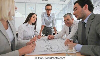 Female engineer at the head of the team holding a meeting