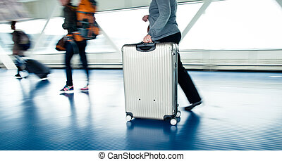 people walking along a corridor - Airport rush: people with...