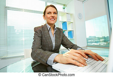 Woman typing - Image of happy businesswoman typing in office
