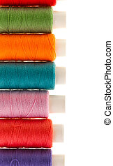 row of bobbins of thread isolated on white background