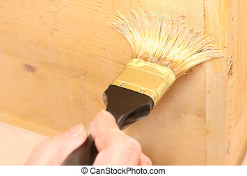 Painting a surface - Human hand holding a brush applying a...