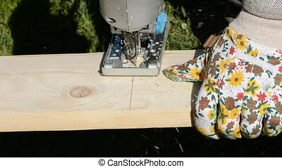 carpenter cutting wooden board with electric saw