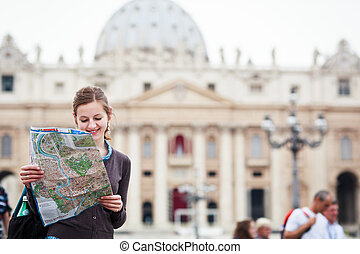 Pretty young female tourist studying a map at St Peters...