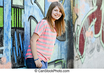 Style teen girl near graffiti wall